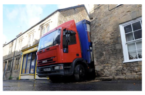 A lorry driver became a laughing stock after he followed his sat nav down a narrow country lane – and got wedged between two buildings.